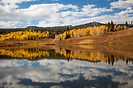 Clouds and an autumn alpine landscape are reflected in the water of Muddy Pass Lake near Steamboat Springs, Colorado.
