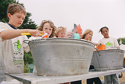 Children washing up plates outside in campsite during environmental awareness camp,