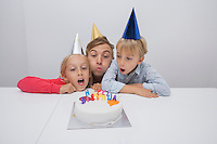 Father and children blowing birthday candles together at table