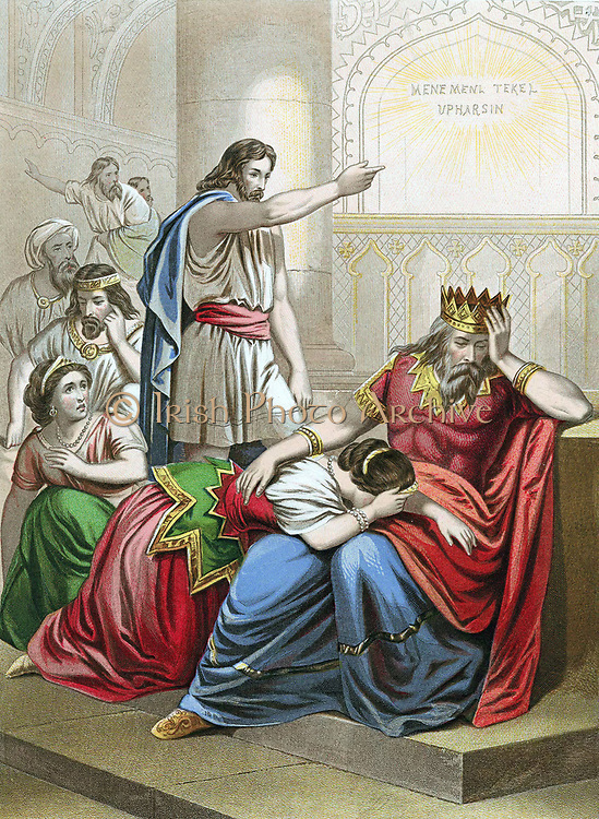 Daniel, one of the four great Hebrew prophets,  interpreting the writing on the wall at Belshazzar king of Babylon's feast, 'Mene Mene Tekel Upharsin' (You are weighed in the scales and found wanting) and foretelling the king's  and his kingdom's downfall. That night Belshazzar was killed. 'Bible' Daniel 5:25 Chromolithograph c1860