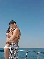 Young couple embracing on yacht smiling side view