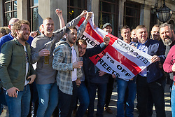London, March 25th 2017. Tens of thousands of protesters in the Unite for Europe march against Brexit take to the streets of London just days after the Westminster terror attack in a show of defiance against extremism and Prime Minister Theresa May's 'hard Brexit'. PICTURED: FOOTBALL FANS with a St George's Flag emblazoned with  'Extremists off our streets' chant slogans outside the St Stephens Arms pub opposite Parliament.