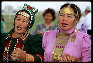 Two costumed young women chant in ritual osuokhai circle dance @ midsummer Ysyakh fest; Yakutsk Russia
