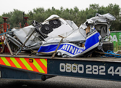 © Licensed to London News Pictures. 26/08/2017. Milton Keynes, UK. Part of the remain of the minius, which is in two pieces, are pictured being removed from scene on the M1 motorway. Police say that several people are dead and four others have been taken to hospital after the accident on the southbound carriageway in the early hours of this morning. Photo credit: Ben Cawthra/LNP