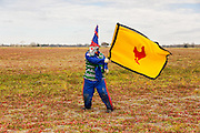 A costumed reveler waves a flag during the Faquetigue Courir de Mardi Gras chicken run on Fat Tuesday February 17, 2015 in Eunice, Louisiana. The traditional Cajun Mardi Gras involves costumed revelers competing to catch a live chicken as they move from house to house throughout the rural community.
