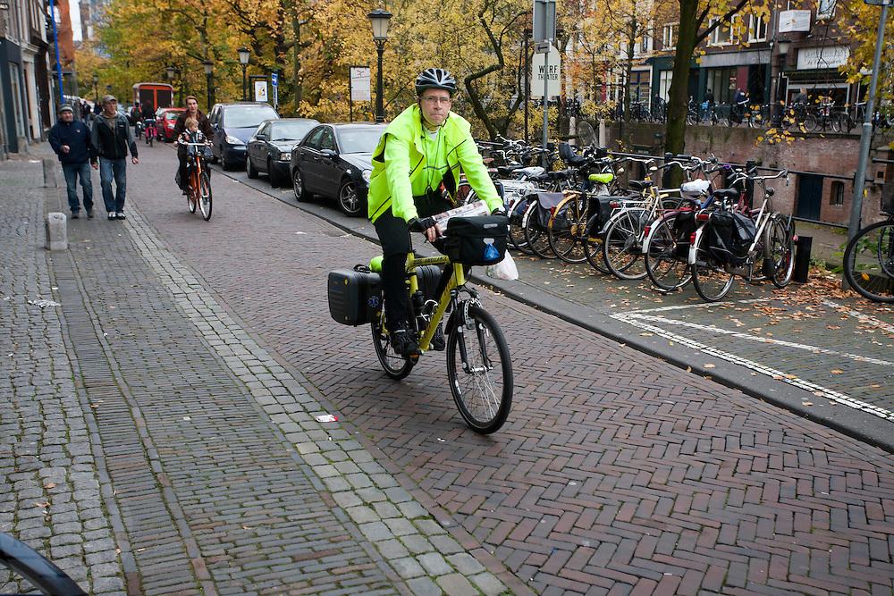 Een medewerker van de ambulancedienst RAVU rijdt op de ambulancefiets over de Oudegracht in Utrecht.<br /> <br /> An employee of the RAVU, the first aid service, is riding the special ambulance bike.