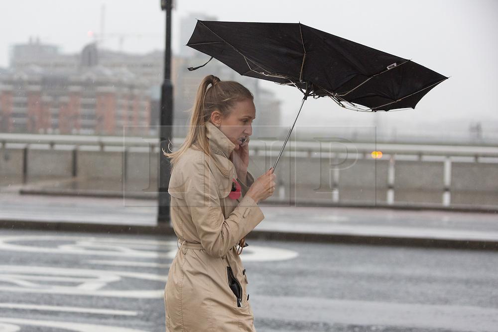 © Licensed to London News Pictures. 17/11/2015. London, UK. A womans umbrella blows inside out whilst she speaks on a mobile phone on London Bridge in London during wet and windy weather today. Photo credit : Vickie Flores/LNP