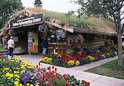 log building with thatched roof,  colorful flowers, Anchorage Visitor Center; Alaska