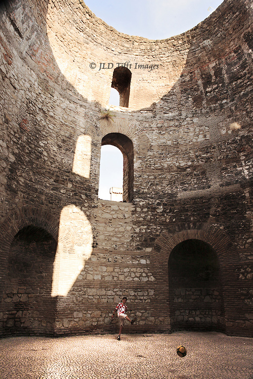 Split, Diocletian's Palace, interior view showing part of the oculus, several arched window openings, and restored floor where a young teenaged boy practices his ball kicking skills.