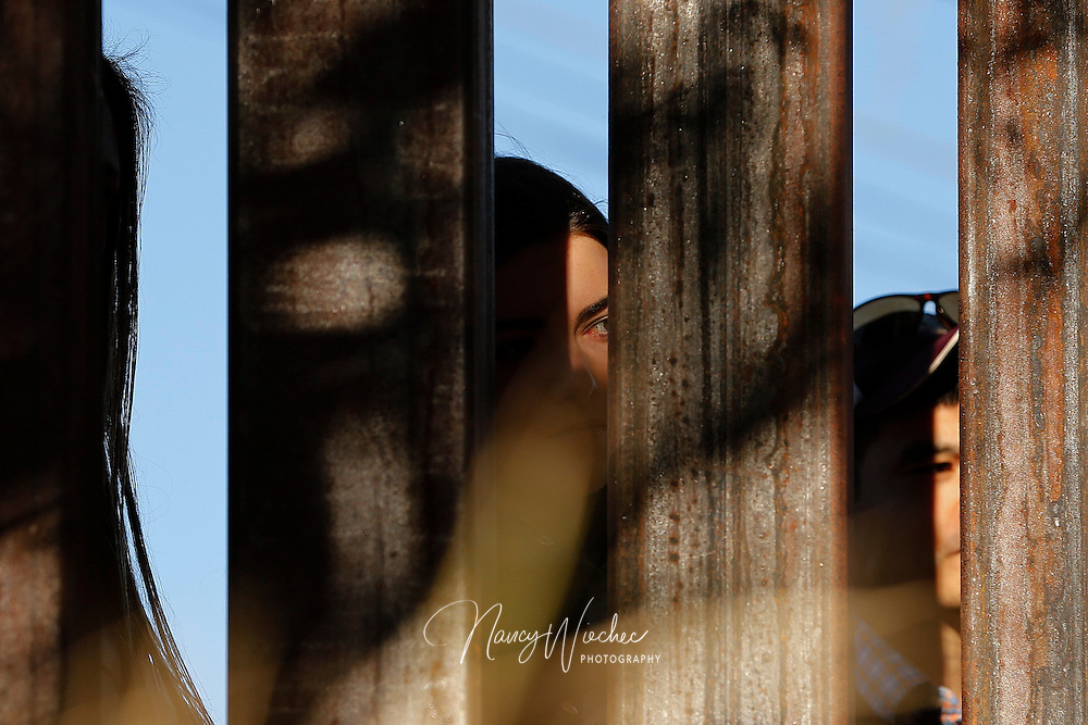 "People peek through the slats of the international border fence as a ""posada"" takes place in Nogales, Sonora, Dec. 20. The annual event held by the Kino Border Initiative and Dioceses Without Borders reflected on the struggles of migrants and migrant families. (CNS photo/Nancy Wiechec)"