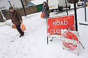 A Closed Road sign and local shoppers passes-by on a hill in south London during wintry snows.