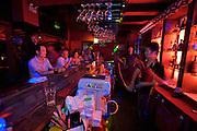 Huhai and Qianhai Lake nightlife district. A bar tender showing his juggling tricks at Alpha & Omega Club.