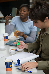 University students drinking coffee and having a snack in the Student's Union whilst working,