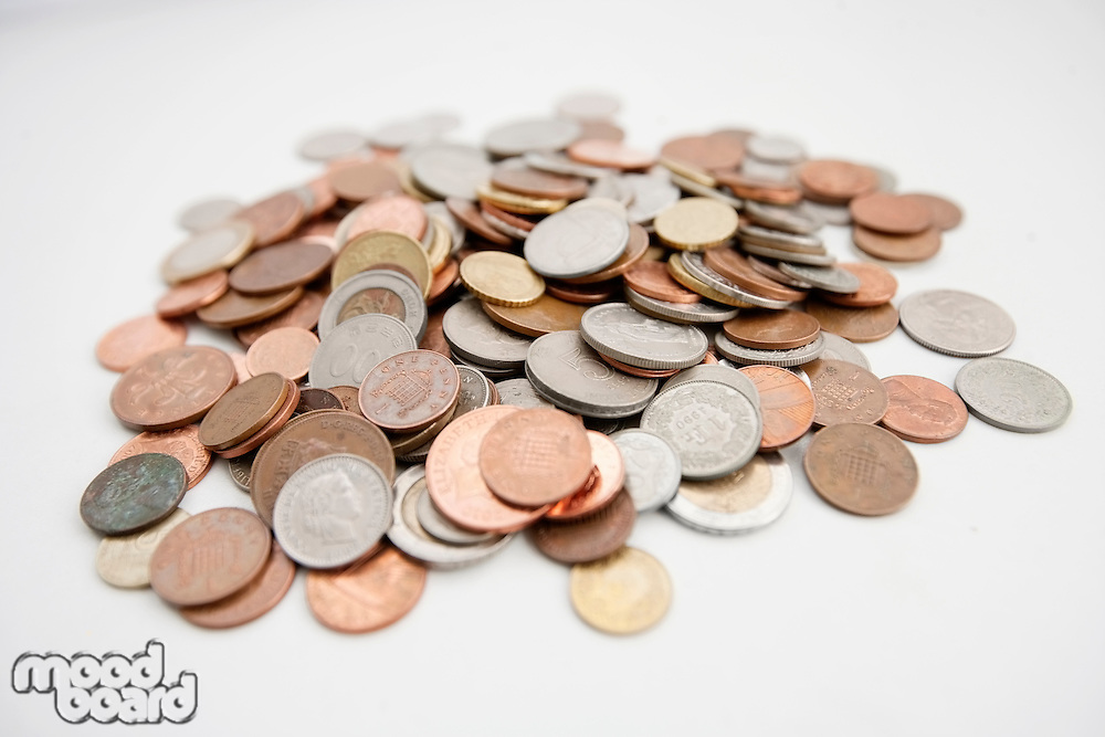Close-up of large group of coins over white background