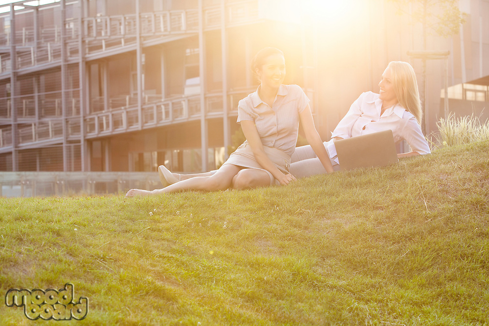 Happy young businesswomen with laptop on office lawn