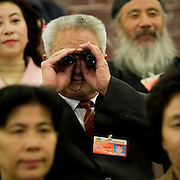 A delegate uses binoculars to observe a session of the National People's Congress after a session in the Great Hall of the People. Chinese leaders are trying to improve energy efficiency to reduce both environmental damage and China's reliance on imported oil, which they see as a strategic weakness.
