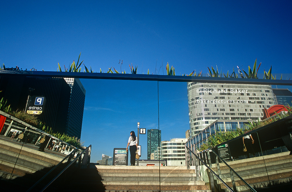 A lone figure of a woman reflected in a large mirror as she walks through La Defence in central Paris.