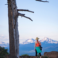 Woman hiking on Black Butte summit in Central Oregon with views of the Sisters Mountains in the background.