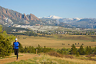 A mid-adult man trail running  on Marshall Mesa outside Boulder, CO