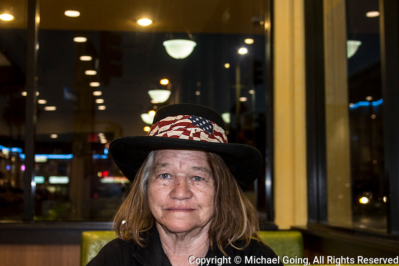 Woman with American Flag headband sitting in fast food restaurant on 4th July