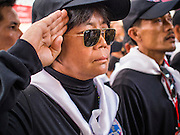 28 APRIL 2014 - BANGKOK, THAILAND: Red Shirt security guards salute as the coffin bearing Kamol Duangphasuk, 45,passes them during his funeral in Bangkok. Kamol was a popular poet who wrote under the pen name Mai Nueng Kor Kunthee. Kamol had been writing since the 1980s and was an outspoken critic of the 2006 coup that deposed Thaksin Shinawatra. After the 2010 military crackdown against the Red Shirts he went into temporary self imposed exile fearing for his safety. After he returned to Thailand he organized weekly protests against Thailand's Lese Majeste laws, which he said were being used to stifle dissent. Kamol was shot and murdered on April 23. The assailants are still at large but the murder is thought to be political.     PHOTO BY JACK KURTZ