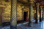 A young novice monk enters the buddhist temple of Wat Mai, via its eleborately decorated golden portico.