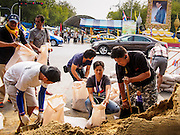 """30 DECEMBER 2013 - BANGKOK, THAILAND: Anti-government protestors fill sandbags to place across Ratchadamnoen Road in Bangkok. Violence around the anti-government protest sites has escalated in recent days and several protestors have been hurt by small explosive devices thrown at their guard posts. As a result, protestors are fortifying their positions with sandbags and bunkers. Suthep Thaugsuban, the leader of the anti-government protests in Bangkok, has called for a new series of massive protests after the 1st of the year and said it the shutdown, or what he described was the seizure of the capital, would be the day when """"People's Revolution"""" would """"begin to end and uproot the Thaksin regime.""""          PHOTO BY JACK KURTZ"""