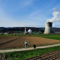 WOman walking her dog in teh countryside close to Leibstadt nuclear power station, which stands close to the German border.<br />