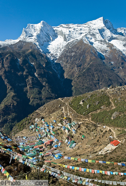 The village of Namche Bazaar (11,220 feet elevation) as seen in 2007. The mountain of Kongde Ri (sometimes called Kwangde Ri; 20,320 feet elevation) rises 4 kilometers west, in the Himalaya of eastern Nepal. Sagarmatha National Park was created in 1976 and honored as a UNESCO World Heritage Site in 1979.