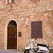 Vespa PX125E scooter parked next to home on street in Montepulciano, Tuscany, Italy<br />