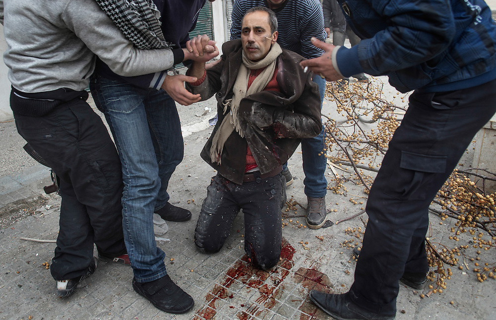 Men help a wounded civilian after a mortar attack in the Saif al-Dawlah neighborhood of Aleppo. The area is immersed in a Syrian civil war that the United Nations estimates has killed more than 60,000 people since the revolt against President Bashar Assad began in March 2011