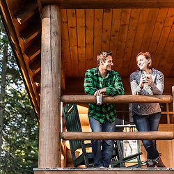 A young couple enjoy an evening on the porch of a cabin at the Appalachian Mountain Club's Gorman Chairback Lodge. Near Greenville, Maine.