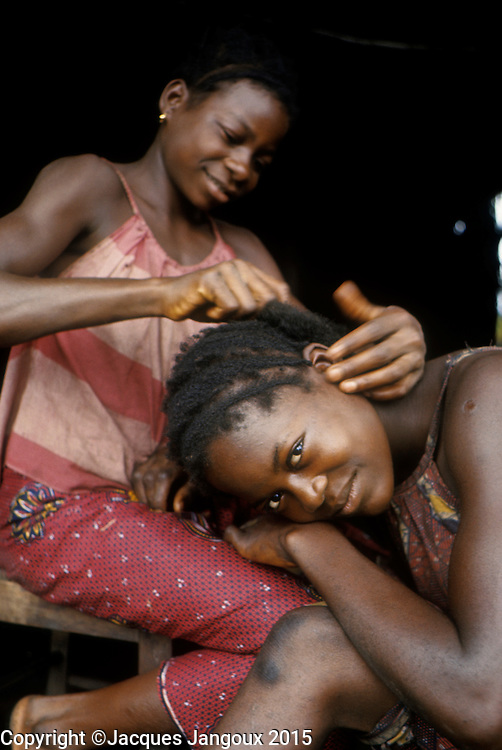 Africa, Democratic Republic of the Congo, Ngiri River area, Libinza tribe. Girl grooming another girl's hair.