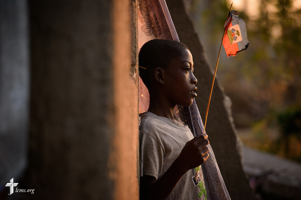 A young boy plays with a Haitian flag outside his severely damaged home from Hurricane Matthew, on Wednesday, Oct. 12, 2016, in a rural area of Les Cayes, Haiti. LCMS Communications/Erik M. Lunsford