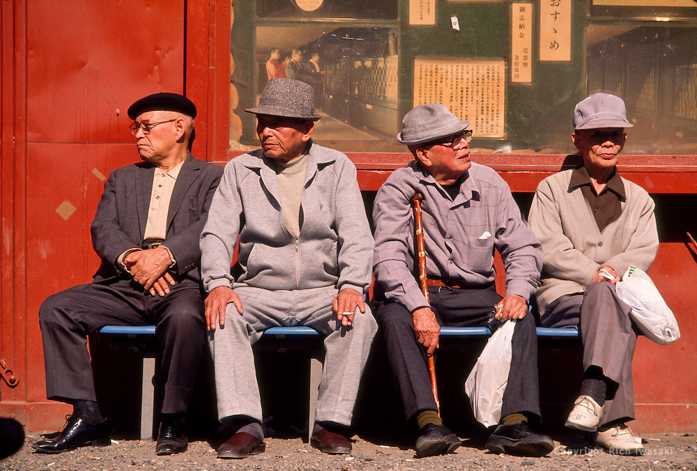 Elderly men sit on bench at Senso-ji (temple), Asakusa district, Tokyo, Japan. The temple is also known as Asakusa Kannon temple.