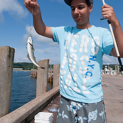 Teenager Jesse Gange holds up a fish he just caught from a dock in North Head, Grand Manan Island. Fishing has forever been a way of life-and fun-on Grand Manan. But as fish stocks are depleted in the Bay of Fundy, the fishing the island has always survived on is disappearing.  Photo by William Drumm.