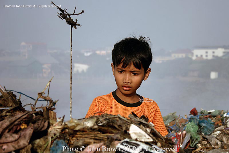 A young worker uses his gaff to collect recyclable material at The Stung Meanchey Landfill in Phnom Penh, Cambodia. Over 700 tons of garbage is dumped there daily.