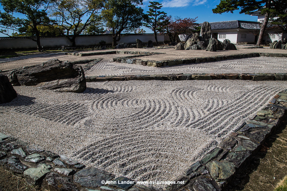 "Hachijin-no-Niwa Garden at Kishiwada Castle - a very unique karesansui garden  set in the courtyard of Kishiwada-jo and designed to be viewed from the windows of the castle. It is a very modern design of geometric, linear stones punctuated by rocks in a field of pebbles. The garden was designed by Mirei Shigemori, a leading figure in the development of the modern Japanese garden. Eight groups of rocks represent the ""Battle Formation of the Eight Positions"". Each of these eight groupings has a name: heaven, earth, phoenix, dragon, cloud, serpent, tiger and wind.  The garden challenges our thinking about the usually calm effect of stone gardens. Based on the layout of a mythological battle conducted by Chinese General Zhuge Liang, the stone setting at the center of the design, named Central Camp, is the garden's focal point."