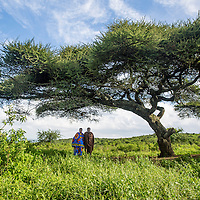 A fistula survivor and her supportive husband stand together beneath a tree near their house.