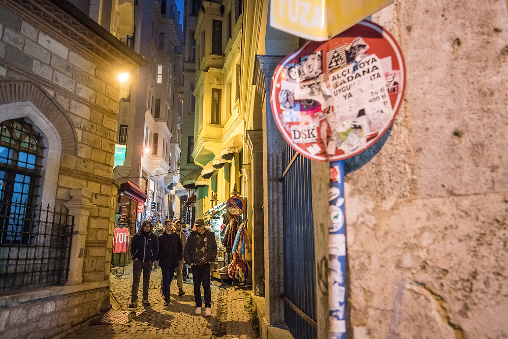 Group of people walk together down narrow street in between buildings in Istanbul, Turkey