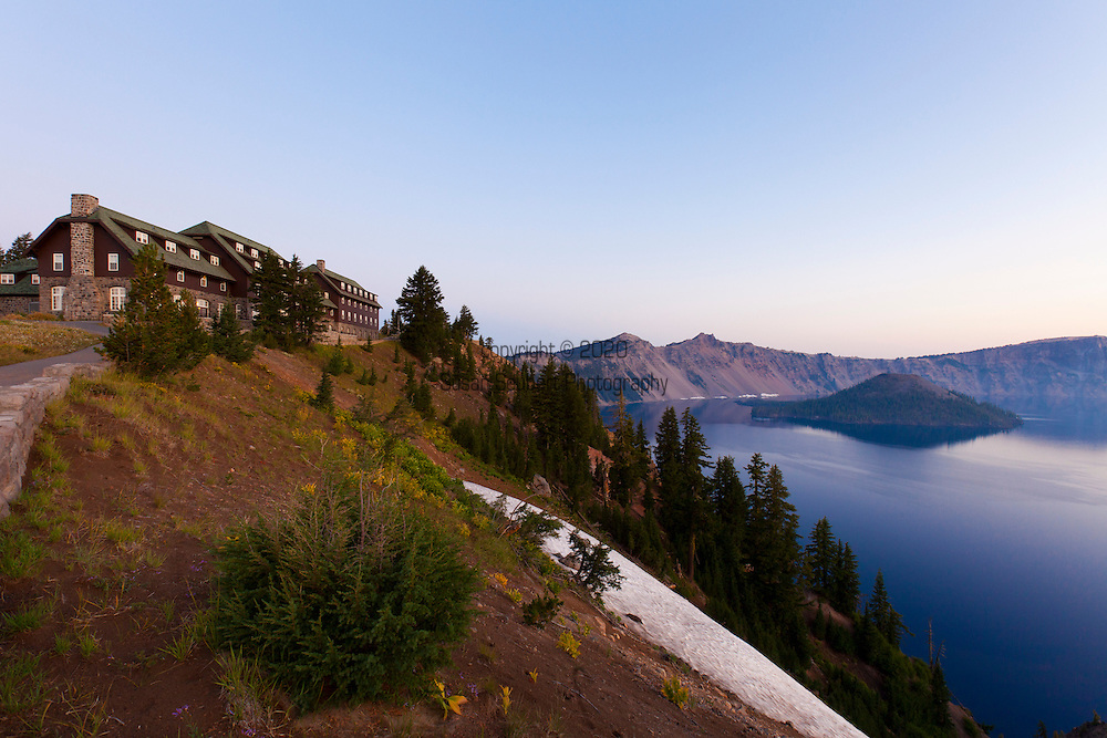"""Crater Lake National Park, the only National Park in the state of Oregon, attracts some 482,000 people annualy. The lake itself is 592 meters (1,943ft) deep and is the deepest lake in the United States.  The park was founded in 1902 and seeks to preserve the natural and cultural resources.  Crater Lake lies in a caldera, or volcanic basin, created when Mt. Mazama collapsed around 7,700 years ago.  The clarity and blueness of the water are unique to this geologic area.  The lake is filled almost entirely by melted snow.  The lake is only accessibly by one trail, the Cleetwood Cove Trail, which leads down to the water for access to the tourist boats.  Pictured here is the historic Crater Lake lodge, the only """"in-park"""" lodging."""