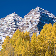 Peaks of the Maroon Bells with yellow aspens during fall in Colorado