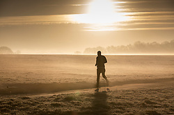 © Licensed to London News Pictures. 21/01/2020. Epsom, UK. An early morning jogger braves a frosty and foggy start to the day on Epsom Downs racecourse in Surrey. Photo credit: Peter Macdiarmid/LNP