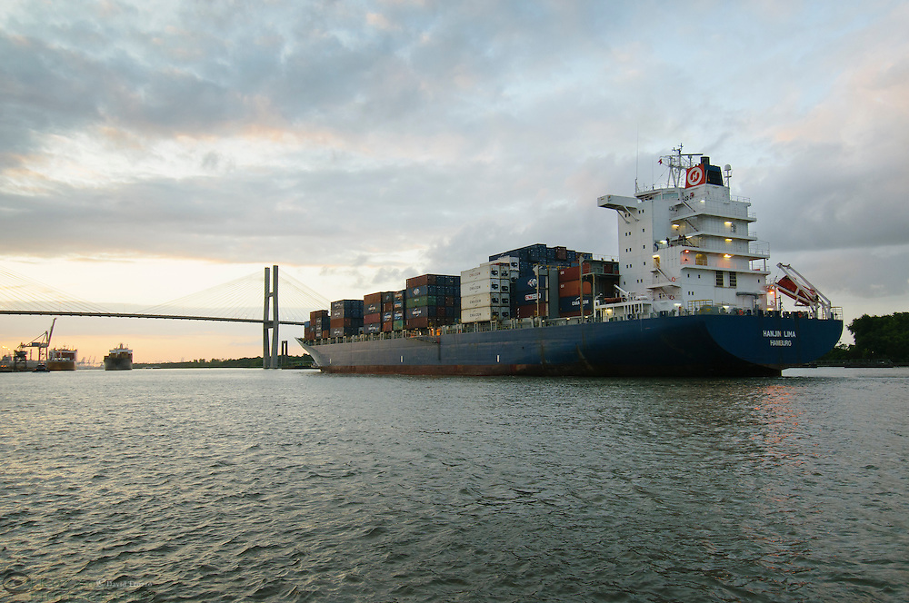 A cargo ship navagates to pass under the Talmadge Memorial Bridge in Savannah, Georgia at sunset..
