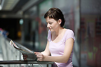 Young woman reading newspaper in shopping centre Voronezh