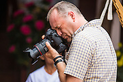 29 JUNE 2014 - DAN SAI, LOEI, THAILAND:  Travel photographer Gavin Gough photographs a merit making ceremony at the Phi Ta Khon (Ghost Festival) in Dan Sai, Loei province, Thailand.    PHOTO BY JACK KURTZ