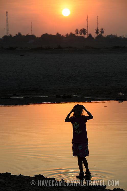 A young Lao girl plays in the shallow, still water of the Mekong River and is silhouetted against the setting sun in the disance. Vientiane, Laos.