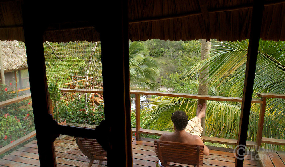 A guest relaxes on the porch of one of the villas at the Blancaneaux Lodge, one of Francis Ford Coppola's resorts, in the eastern part of Belize.<br />JUSTIN LANE FOR THE NEW YORK TIMES