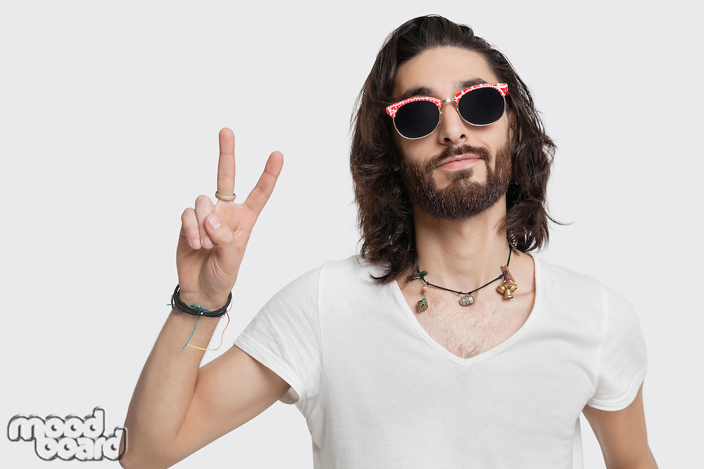 Portrait of young man wearing sunglasses gestures peace sign against white background