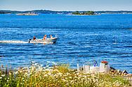 Människor på väg till Sandhamn i en liten öppen motorbåt skärgården
